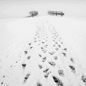 foot steps on the snow showing distance to wooden bridge