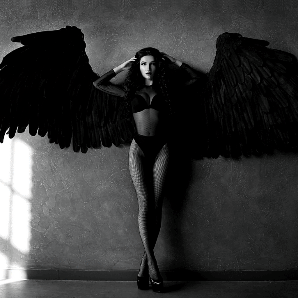 a white woman with black wings standing wearing a sexy pair of lingerie