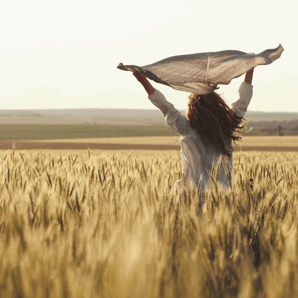 woman in the middle of field holding a scarf up high