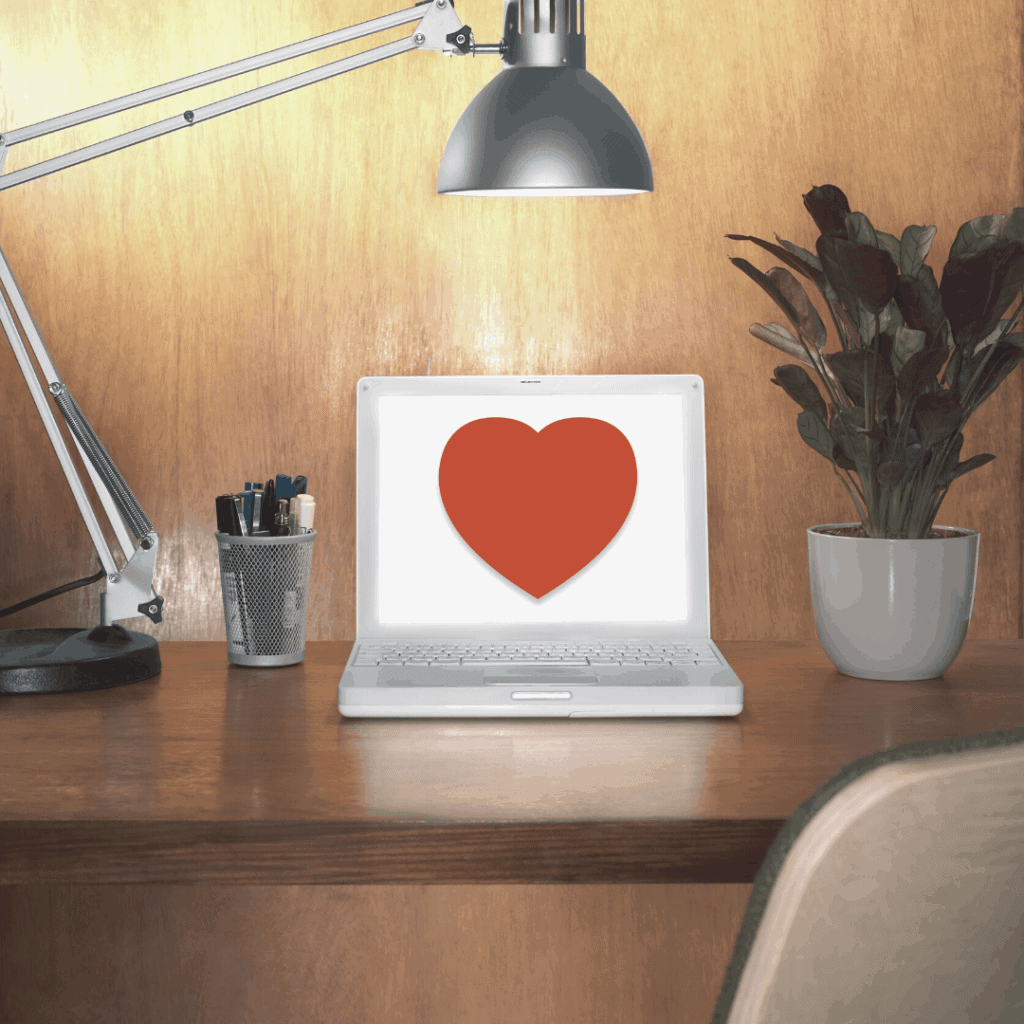 a laptop online with a heart on top of desk focused by a lamp