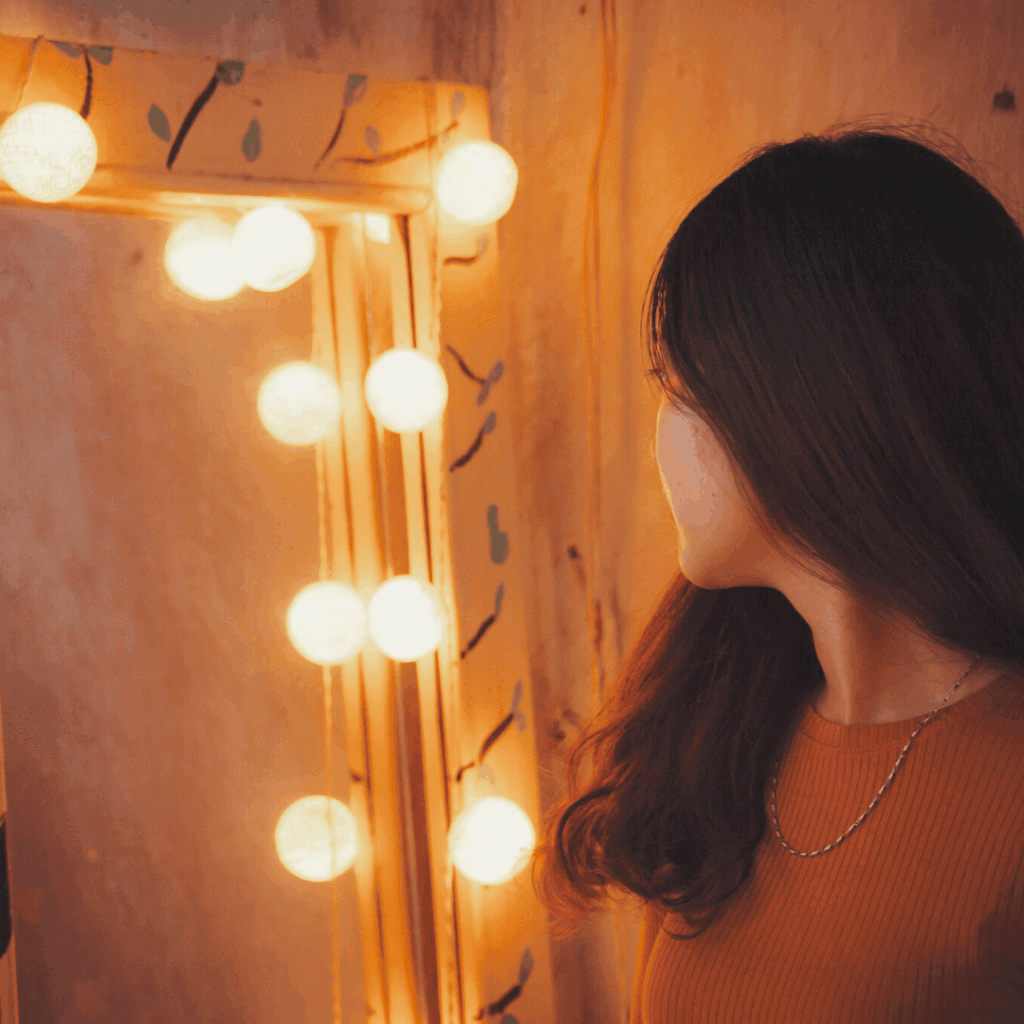 woman facing mirror with lights