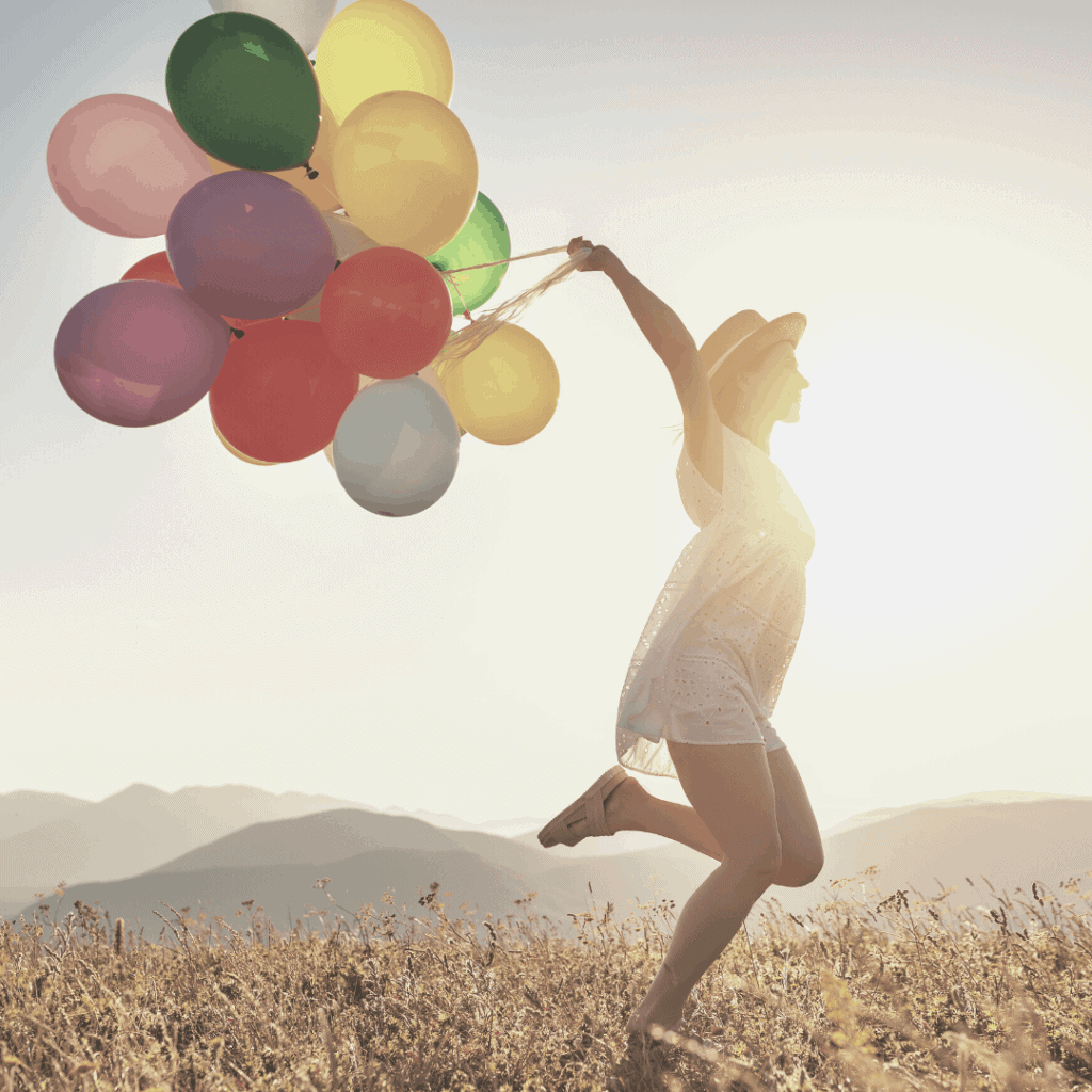 woman holding colorful balloons in front a sunrise