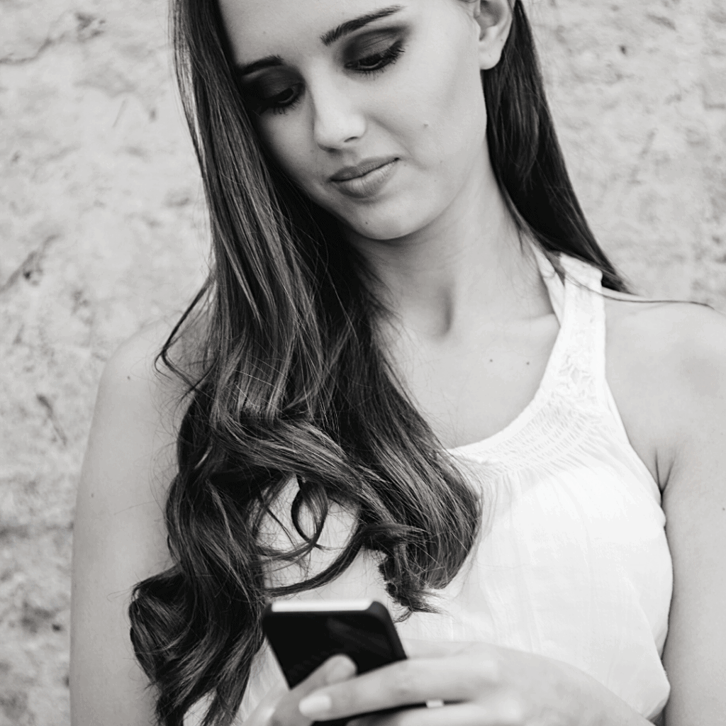 a white woman holding and looking into a mobile phone