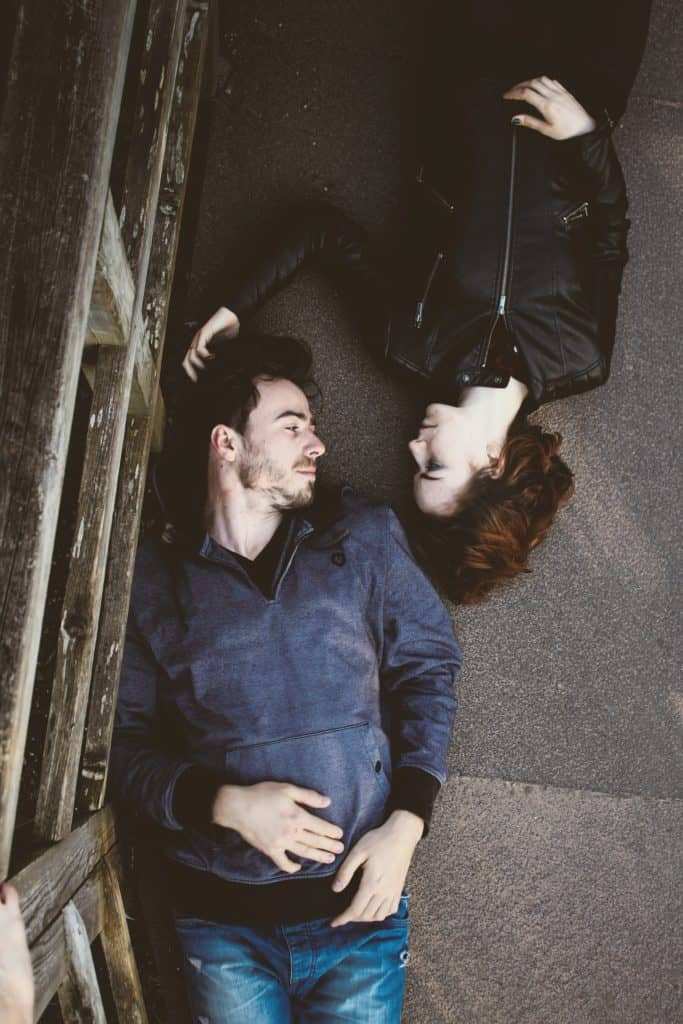 man and woman laying on gray concrete surface looking at each other