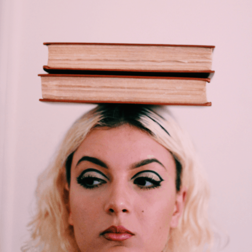 an image of a white blonde woman balancing 2 books on her head with a negative emotion showing on her face
