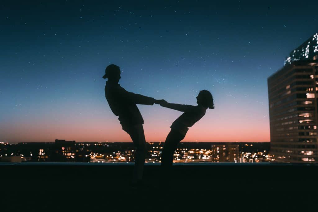 couples on top of a building holding each others hand in front of a city lights view