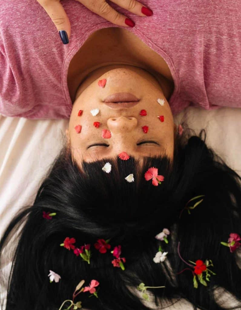 sensual young ethnic lady lying in bed with tiny flowers on her hair, petals on her face and her hands on her chest